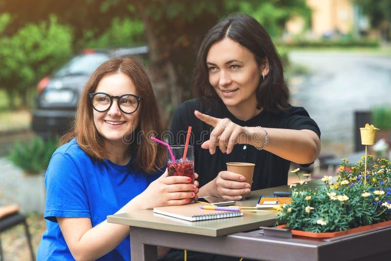 Dois amigos bonitos novos das mulheres têm uma ruptura de café no terraço, falando um com o otro apontar de lado imagens de stock royalty free