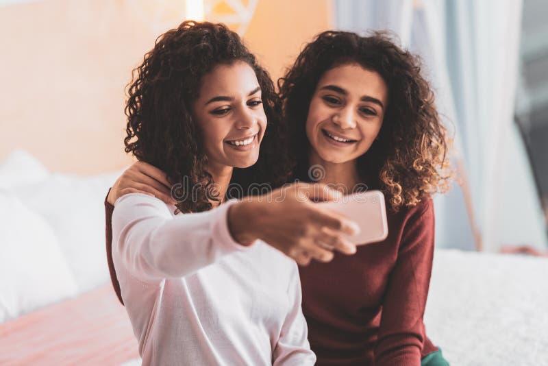 Dois amigos bonitos que sorriem tomando o selfie fotografia de stock