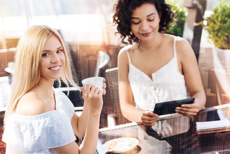 Dois amigos consideravelmente fêmeas que relaxam no café imagens de stock