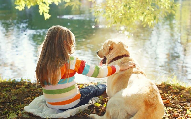 Dois amigos, criança com o cão de labrador retriever que senta-se no verão foto de stock royalty free