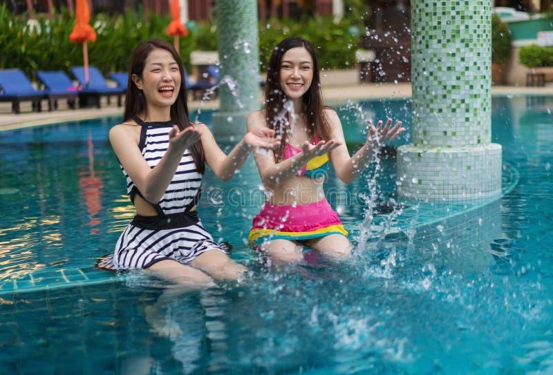 Dois amigos da jovem mulher que espirram a água na piscina fotos de stock royalty free