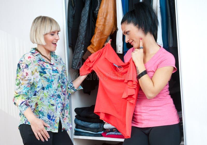 Dois amigos da mulher que escolhem a roupa imagem de stock