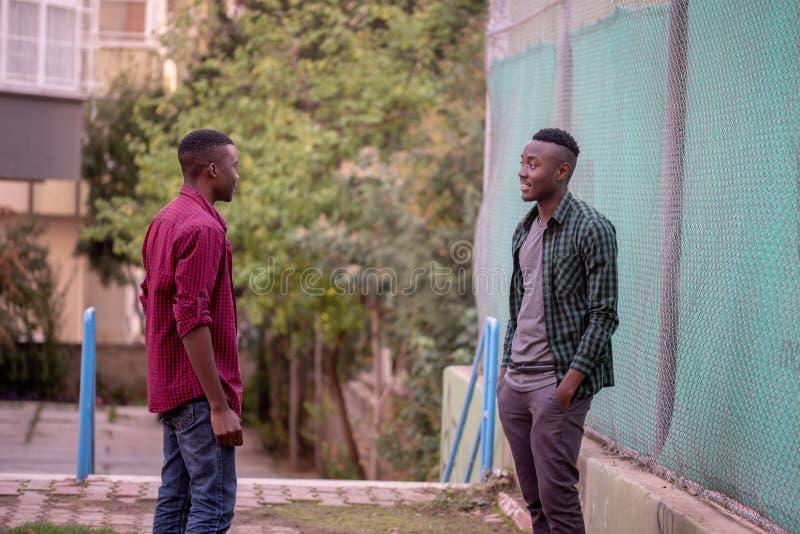Dois amigos da raça preta que conversam na rua Conceito dos amigos imagem de stock