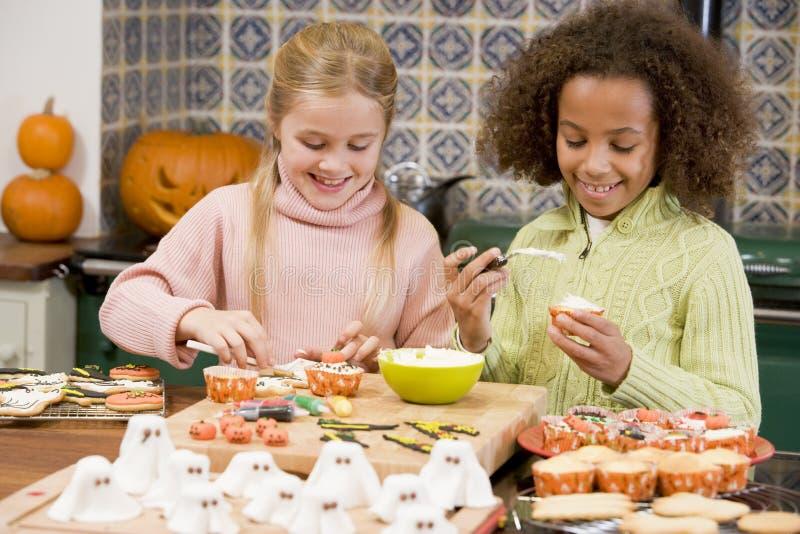 Dois amigos da rapariga em Halloween na cozinha fotos de stock royalty free