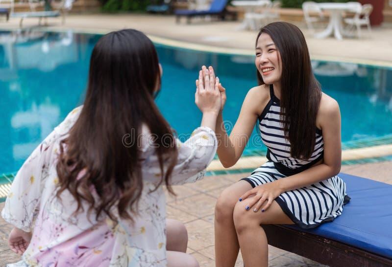 Dois amigos das mulheres apreciam na piscina foto de stock royalty free