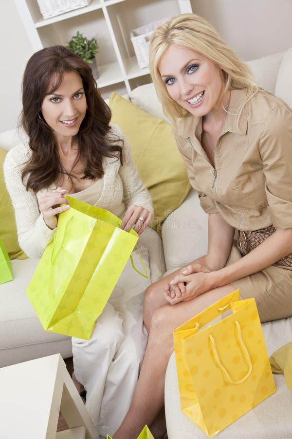 Dois amigos das mulheres com sacos de compra dirigem em casa imagens de stock royalty free