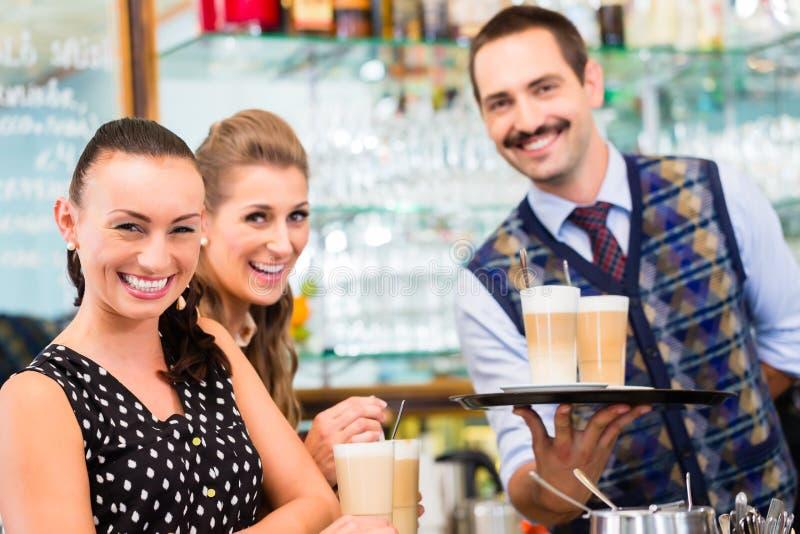 Dois amigos das mulheres no cappuccino bebendo do café imagens de stock
