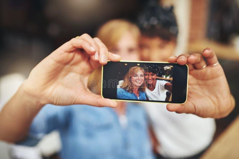 Dois amigos das mulheres que tomam um selfie em um móbil foto de stock royalty free