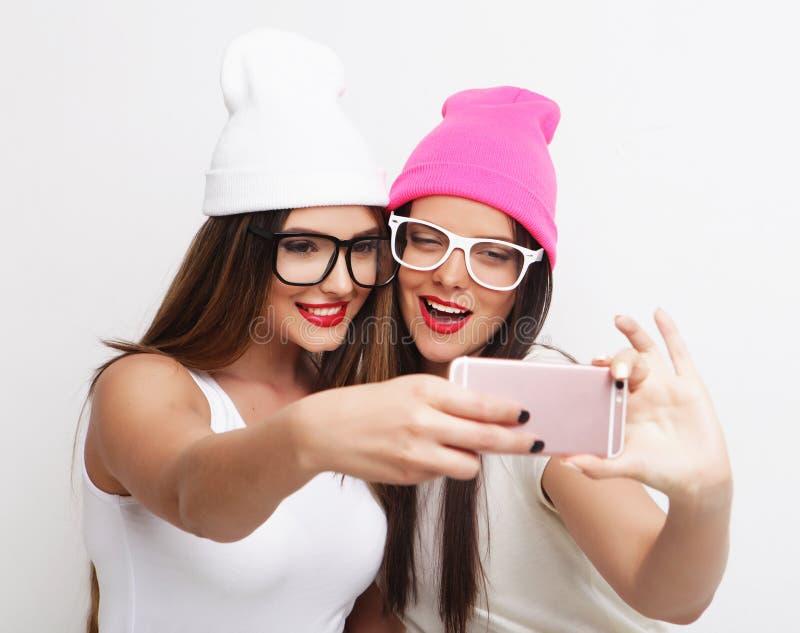 Dois amigos de adolescentes no equipamento do moderno fazem o selfie imagens de stock