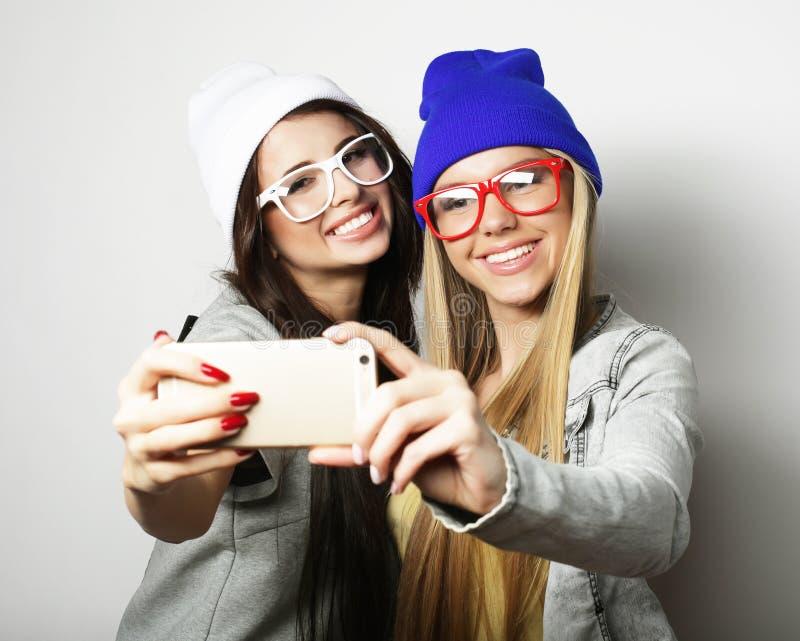 Dois amigos de adolescentes no equipamento do moderno fazem o selfie imagem de stock royalty free