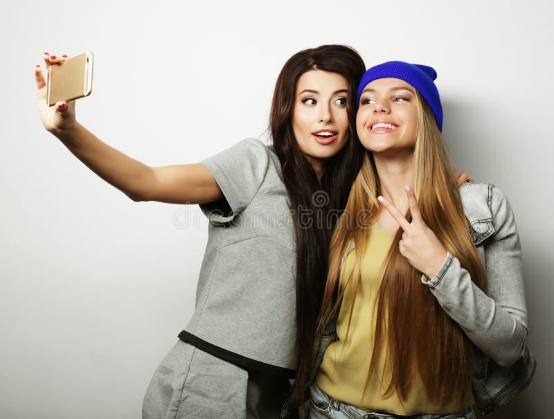 Dois amigos de adolescentes no equipamento do moderno fazem o selfie foto de stock royalty free