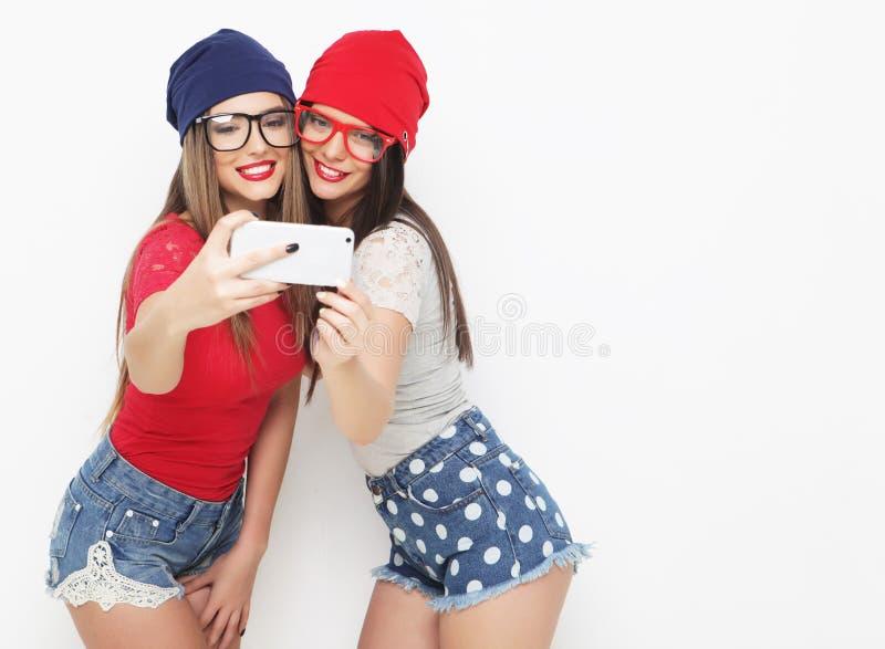 Dois amigos de adolescentes no equipamento do moderno fazem o selfie imagens de stock royalty free