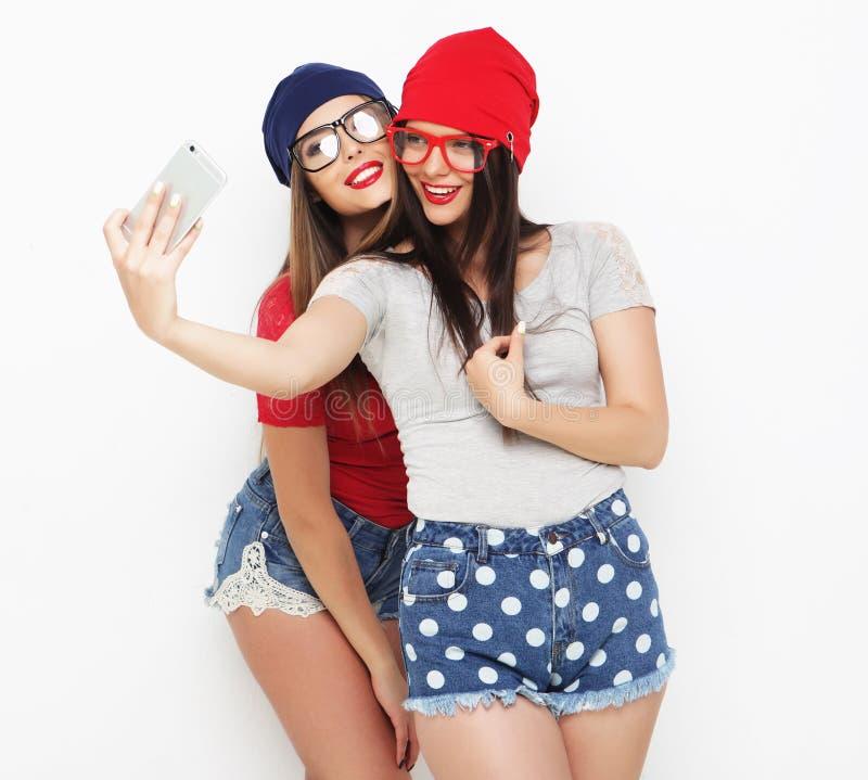 Dois amigos de adolescentes no equipamento do moderno fazem o selfie foto de stock