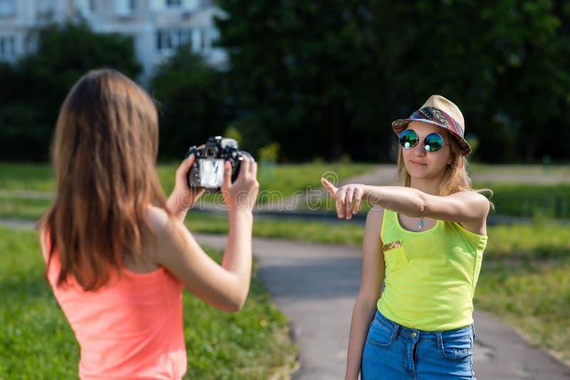 Dois amigos de menina verão na natureza Grava o vídeo As estudantes na mudança fazem fotos Sorrisos felizmente Conceito você pode foto de stock