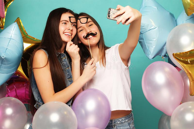 Dois amigos de meninas com balões do colorfoul fazem o selfie em um pH fotos de stock royalty free