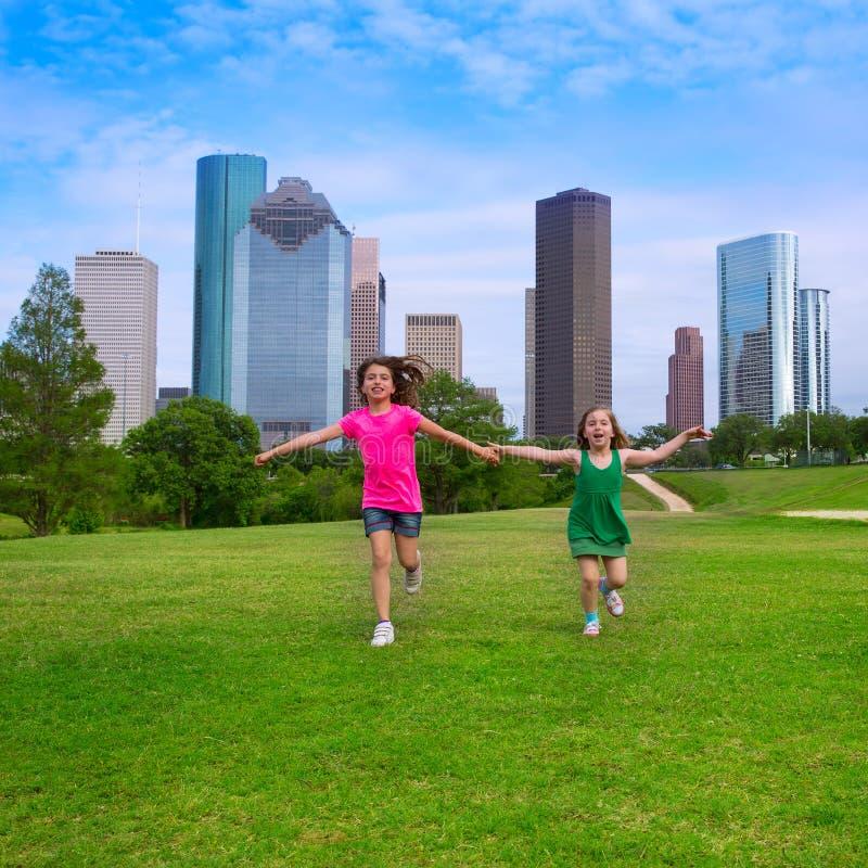 Dois amigos de meninas da irmã que correm guardando a mão na skyline urbana imagem de stock