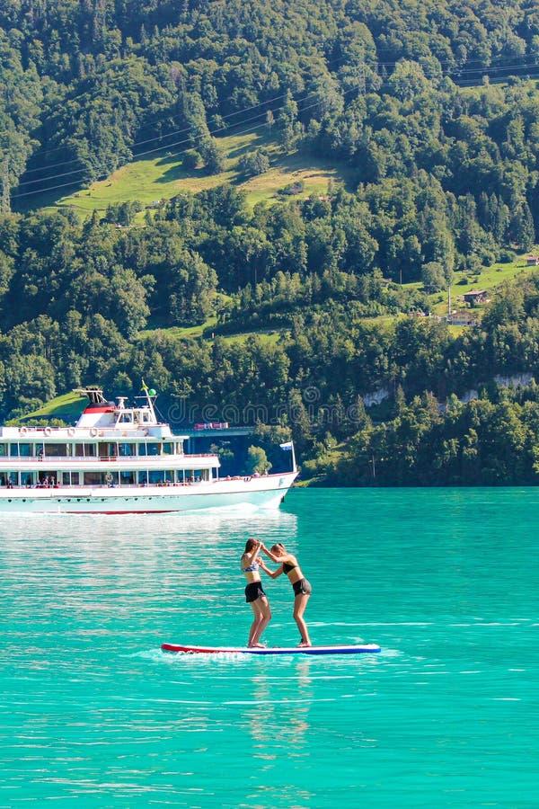 Dois amigos de moça que estão na placa de pá no lago Brienz de turquesa em Suíça Barco de turista no fundo switzerland imagens de stock