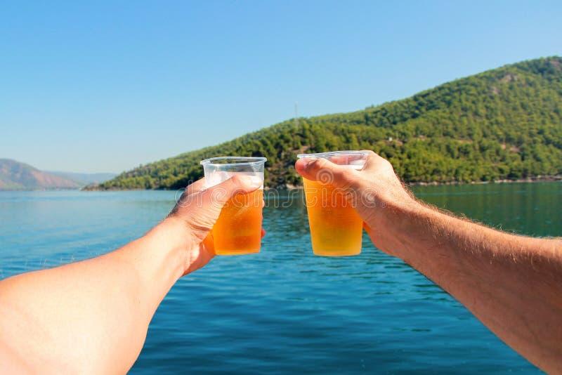 Dois amigos dizem um brinde no mar fotografia de stock royalty free