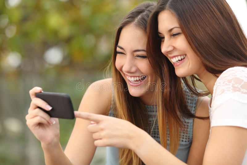 Dois amigos engraçados das mulheres que riem e que compartilham de meios em um telefone esperto foto de stock