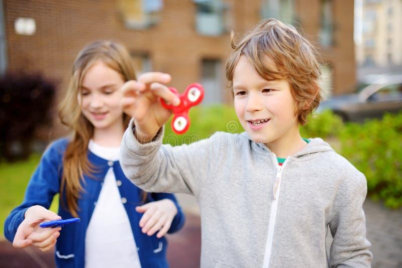 Dois amigos engraçados que jogam com os giradores da inquietação no campo de jogos Brinquedo dealívio popular para crianças e adu imagem de stock