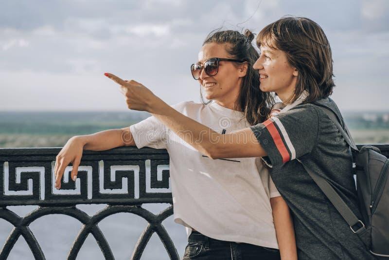 Dois amigos engra?ados que tomam o selfie fora na rua no por do sol com uma luz morna no fundo foto de stock