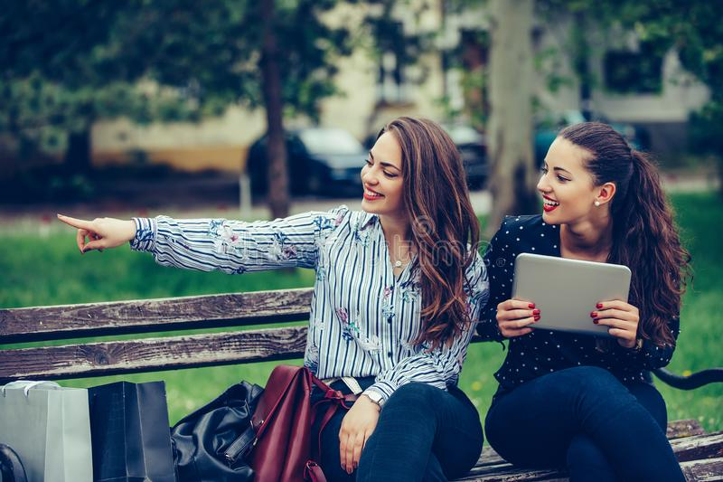 Dois amigos fêmeas bonitos que guardam uma tabuleta digital que aponta afastado na rua fotos de stock