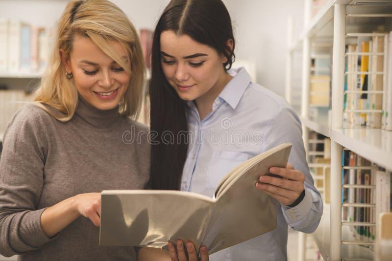 Dois amigos fêmeas da faculdade que estudam um livro na biblioteca imagem de stock royalty free