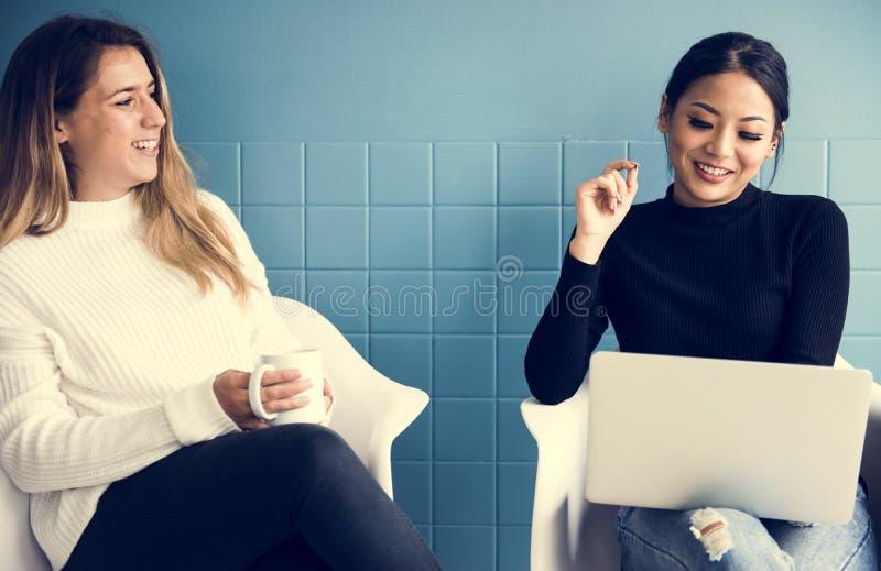 Dois amigos fêmeas estão tendo uma conversação ao comer o café fotos de stock