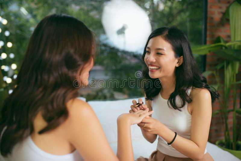Dois amigos fêmeas fazem um tratamento de mãos O conceito do cuidado da mão imagem de stock royalty free