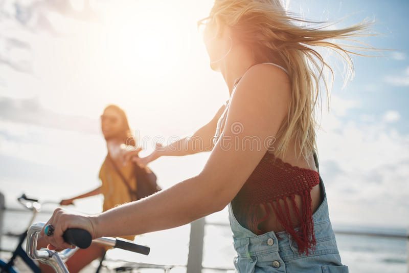 Dois amigos fêmeas novos que montam suas bicicletas imagens de stock