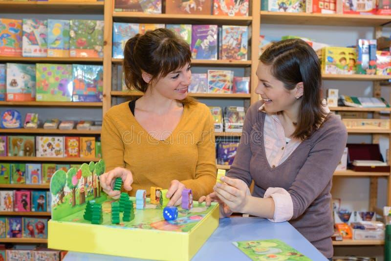 Dois amigos fêmeas que compram brinquedos para suas crianças foto de stock