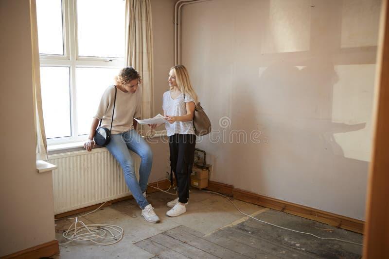 Dois amigos fêmeas que compram a casa pela primeira vez que olha a avaliação da casa na sala ser renovado imagens de stock