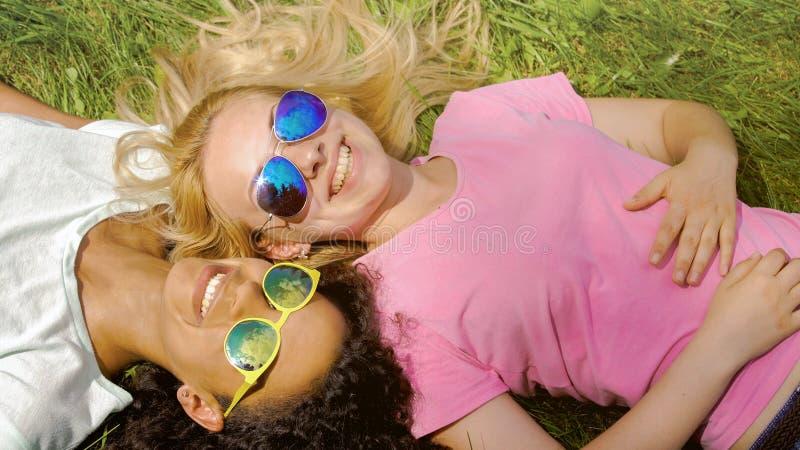 Dois amigos fêmeas que encontram-se na grama no parque, apreciando o fim de semana do verão, amizade fotos de stock