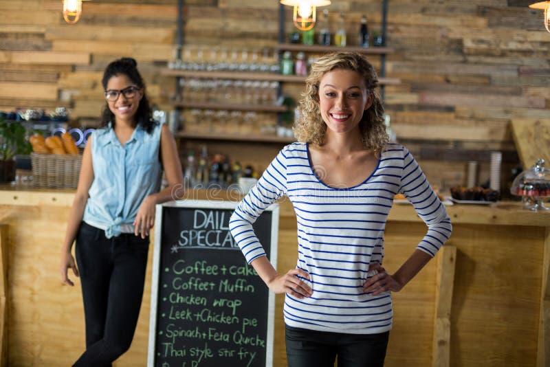 Dois amigos fêmeas que estão com o quadro indicador do menu perto do contador imagens de stock royalty free
