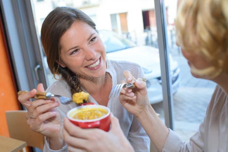 Dois amigos fêmeas que falam na tabela e no sorriso do café foto de stock