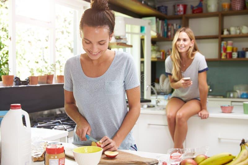 Dois amigos fêmeas que preparam o café da manhã em casa junto imagem de stock