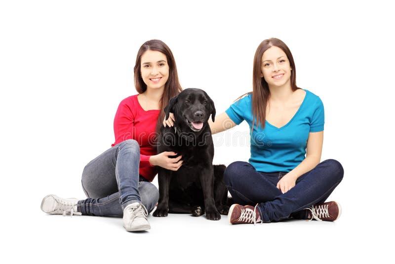 Dois amigos fêmeas que sentam-se em um assoalho e que levantam com um cão imagem de stock