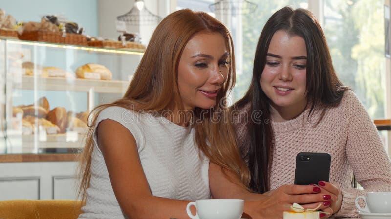 Dois amigos fêmeas que surfam o Internet através do telefone esperto na cafetaria fotos de stock