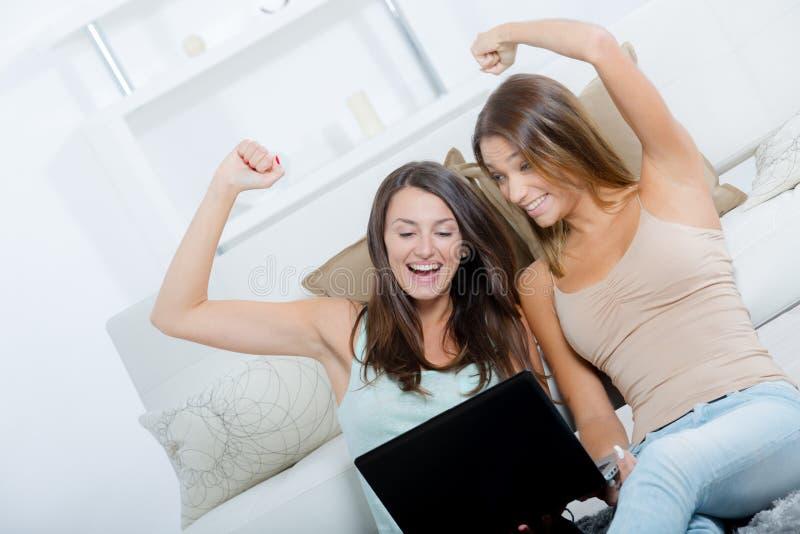 Dois amigos fêmeas que usam o portátil em casa imagem de stock royalty free
