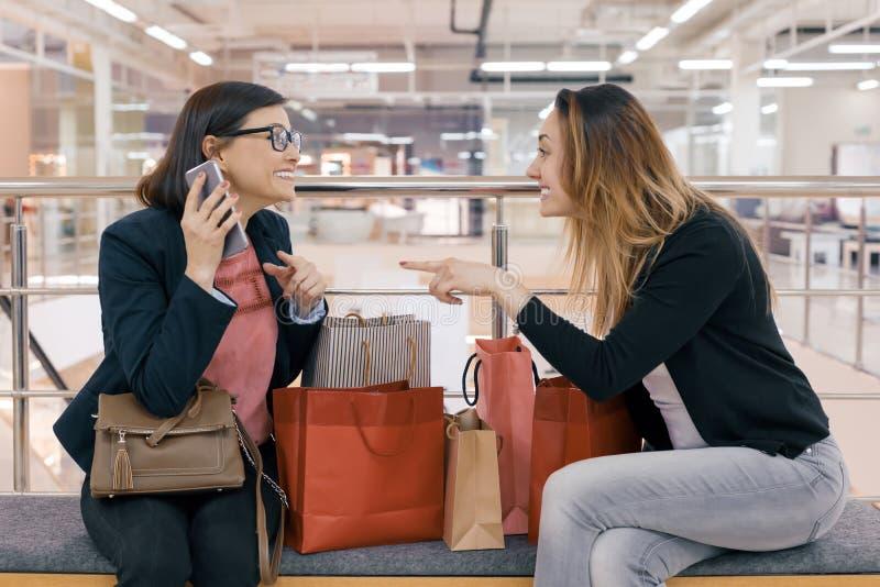 Dois amigos felizes com sacos de compras, mulheres das mulheres adultas que falam o assento na alameda, com muitas compras fotografia de stock royalty free