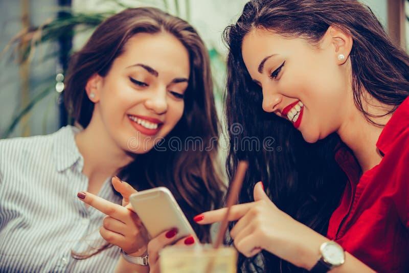 Dois amigos felizes das mulheres que compartilham de meios sociais em um telefone esperto fotografia de stock royalty free