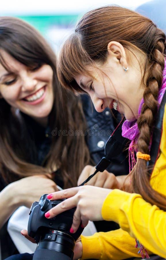 Dois amigos felizes das mulheres que olham fotos na câmara digital imagem de stock royalty free