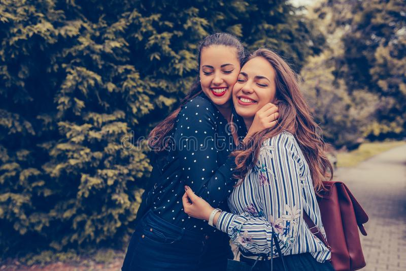 Dois amigos felizes emocionais da mulher que abraçam-se fora fotografia de stock