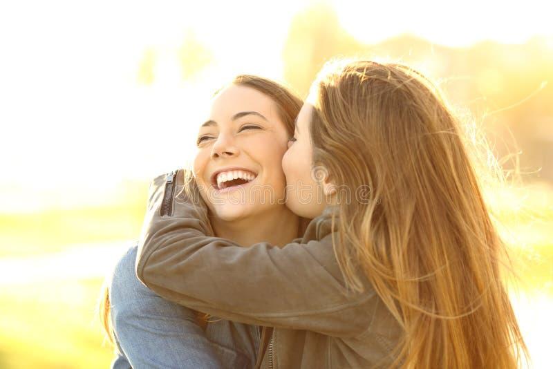 Dois amigos felizes que abraçam e que beijam foto de stock