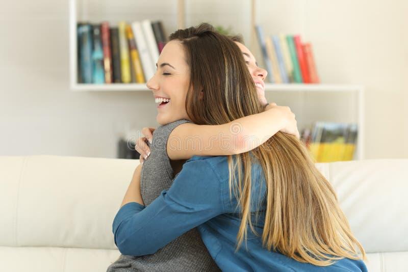 Dois amigos felizes que abraçam em casa foto de stock royalty free