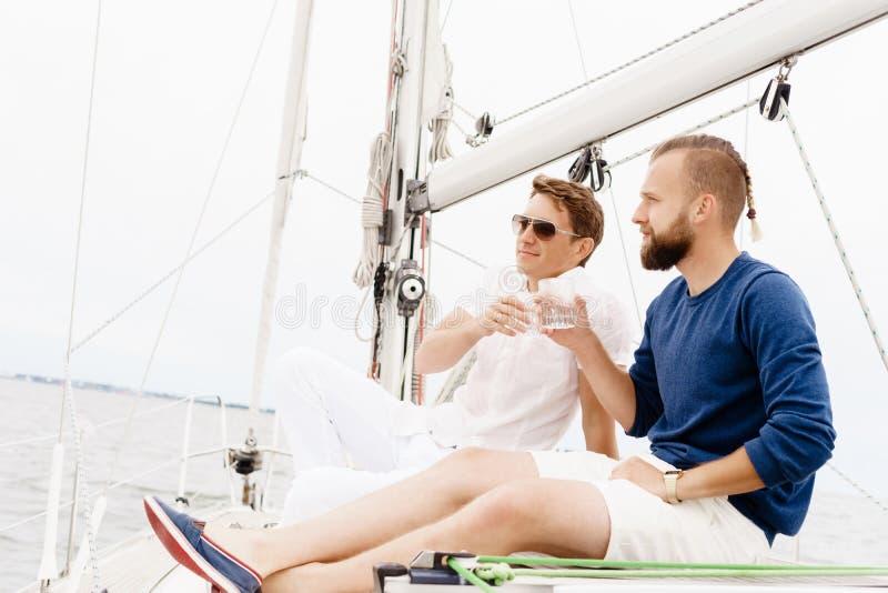 Dois amigos felizes que viajam em um iate Férias, turismo, holid fotos de stock royalty free