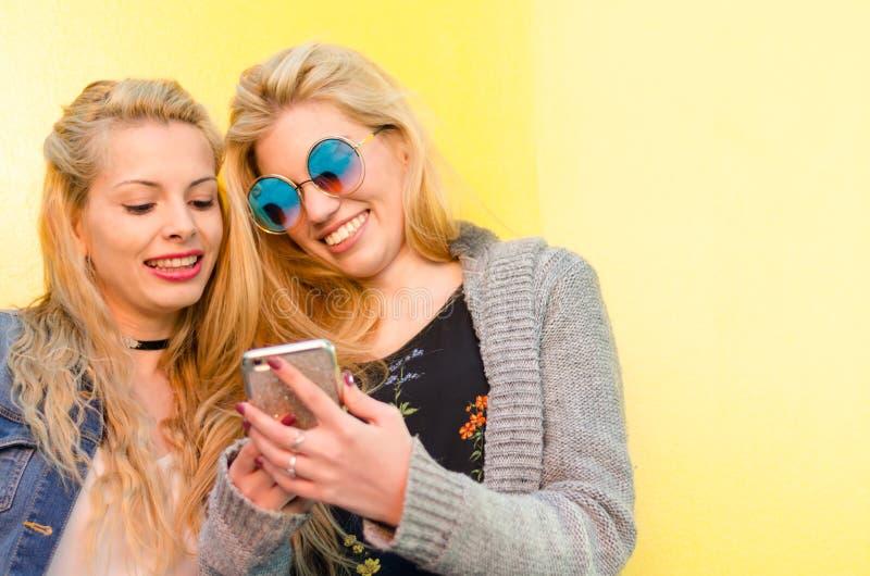 Dois amigos louros dos estudantes que riem usando o telefone celular em uma parede amarela foto de stock