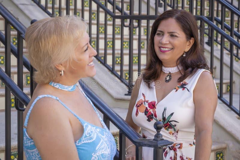 Dois amigos maduros das mulheres param o bate-papo na parte inferior das escadas imagem de stock royalty free