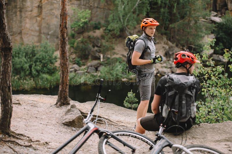 dois amigos masculinos com as trouxas e as bicicletas que descansam perto do rio imagens de stock royalty free