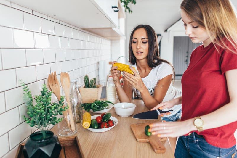 Dois amigos na cozinha preparam a salada e comem o milho imagens de stock royalty free